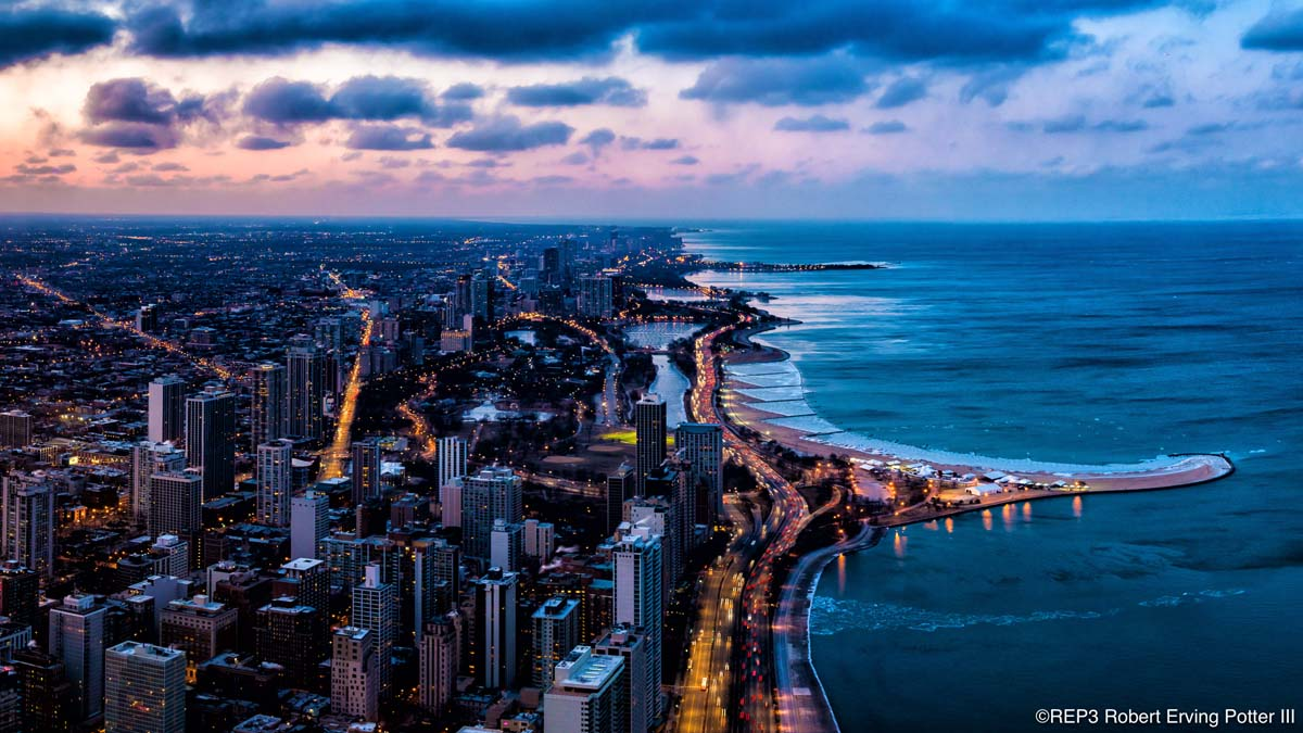 Sunset image of the skyline and lakefront of Chicago, Illinois looking north to the top of the Gold Coast and North Avenue Beach jutting out into Lake Michigan. All rights reserved: REP3.com Robert Erving Potter III 2020
